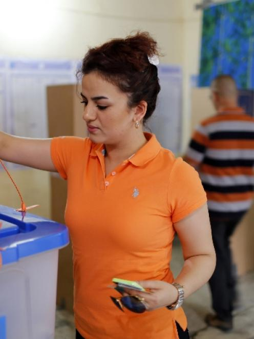 A woman casts her vote at a polling station during a parliamentary election in Baghdad. Photo by...