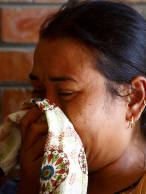 A woman cries as she arrives at a hospital in Kathmandu, where loved ones are undergoing...