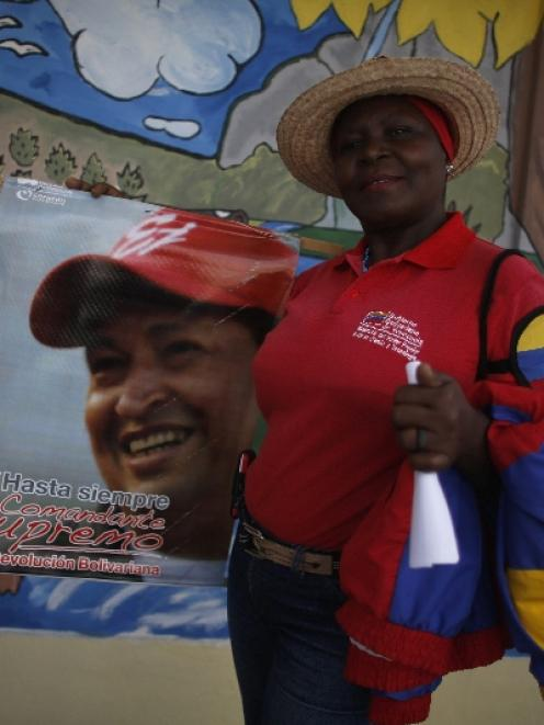 A woman holds a poster of Venezuela's late President Hugo Chavez at the 23 de Enero neighbourhood...