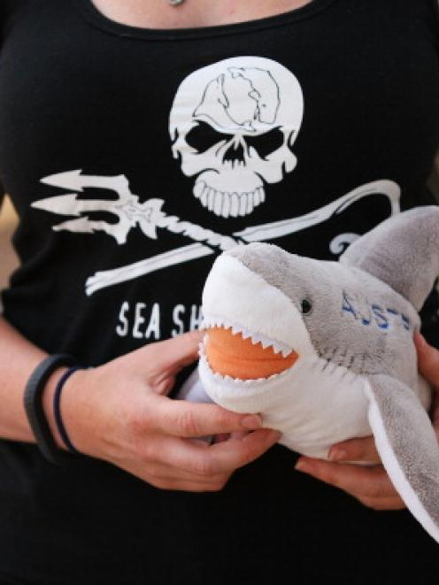 A woman holds a shark plush toy in protest against the catching and killing of sharks in Western...
