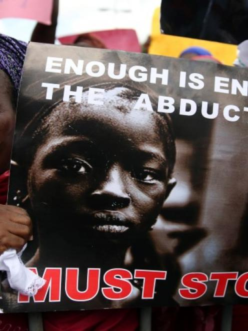 A woman holds a sign during a protest demanding the release of abducted secondary schoolgirls...