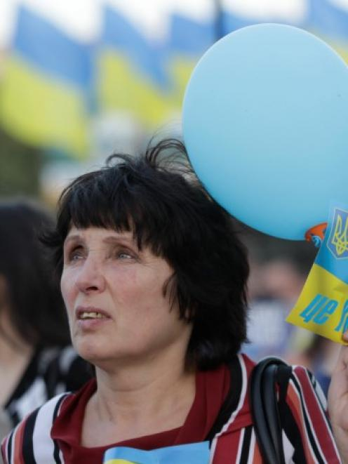 A woman holds balloons in the colours of Ukraine's flag during a pro-Ukrainian rally in the...