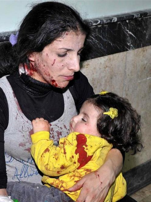 A woman hugs her daughter who was injured in an explosion in Hai al-Wuroud, as they wait in a...
