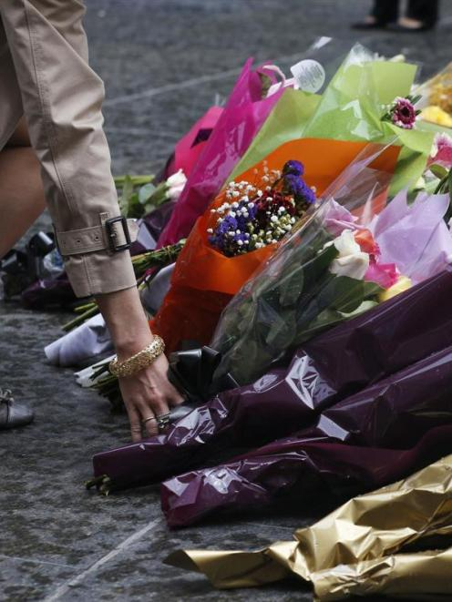 A woman lays a floral tribute to those who died in the Sydney cafe siege, near the site of the...