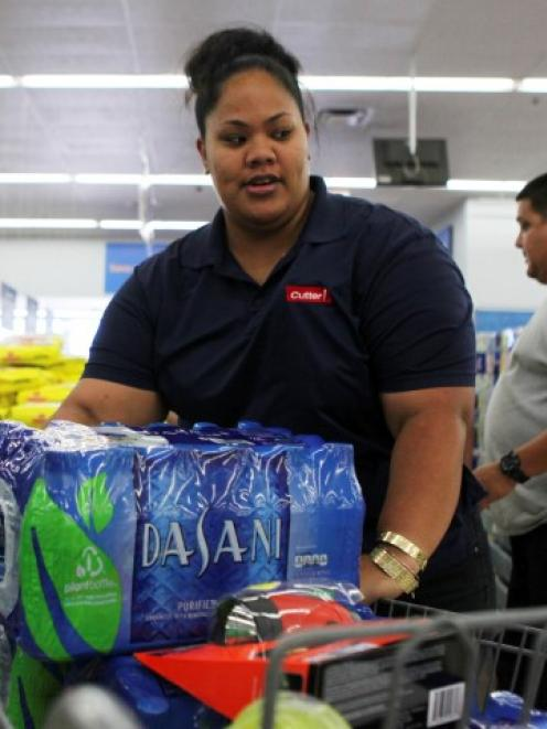 A woman loads bottled water into her shopping cart while buying supplies in Mililani, Hawaii as...