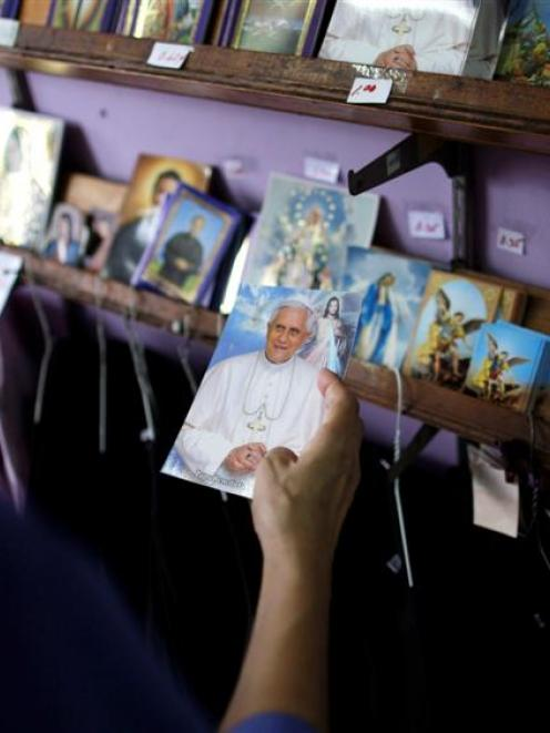 A woman looks at a postcard with a photograph of Pope Benedict XVI inside a church store in...