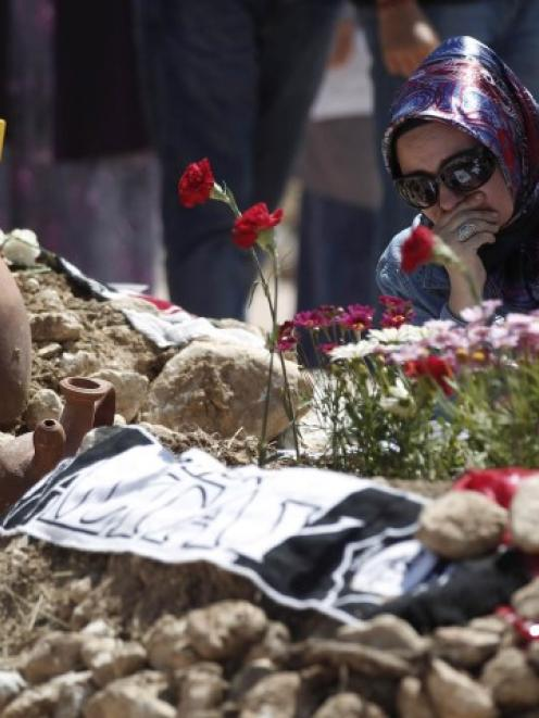 A woman mourns at graves for men killed in the mine disaster, at a cemetery in Soma, a district...