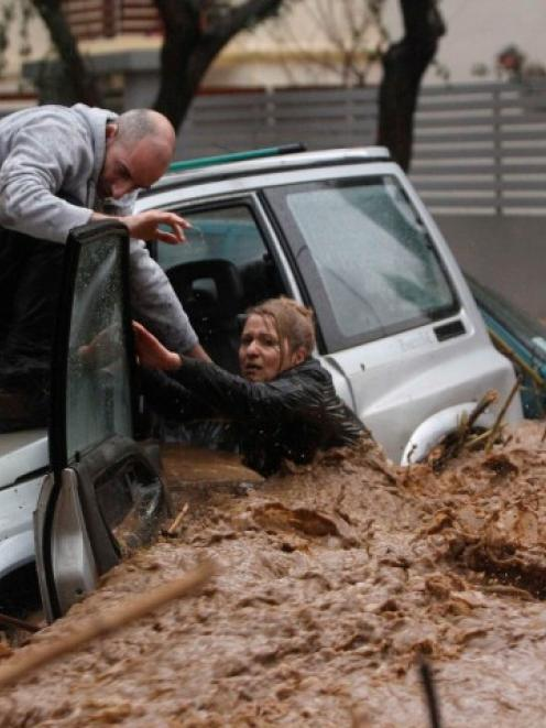 A woman stuck in her car is rescued from floodwaters by a resident during heavy rain in Chalandri...