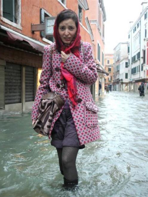 A woman walks in a flooded street in Venice. REUTERS/Manuel Silvestri