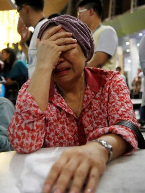 A woman who thinks her sister was on the aircraft cries as she waits for more information at...