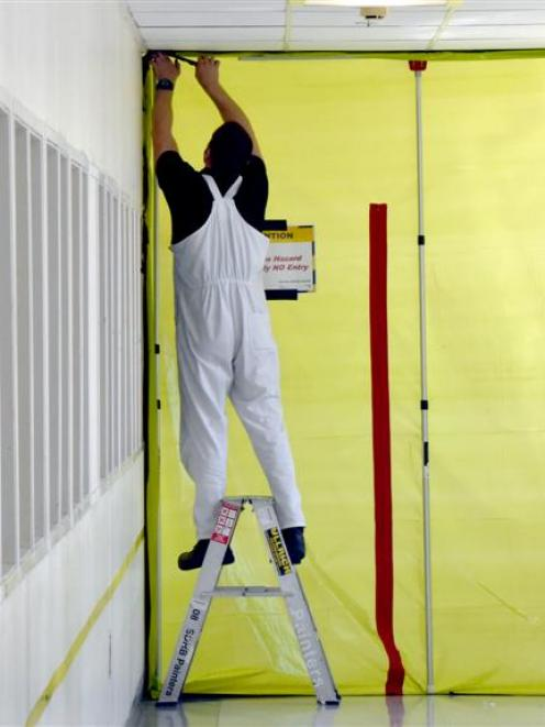 A worker secures screening material to the entrance of the ultrasound suite.