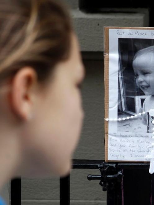 A young girl looks at a makeshift memorial left outside the Krim family apartment in New York....