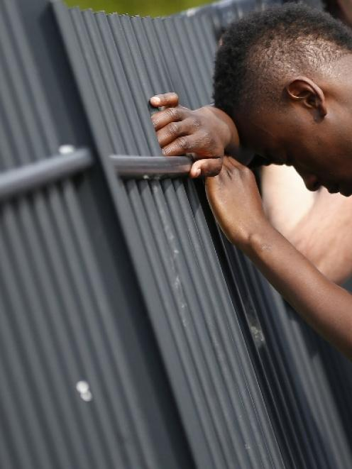 A youth leans against the fence surrounding Corpus Christi Catholic College after teacher Anne...