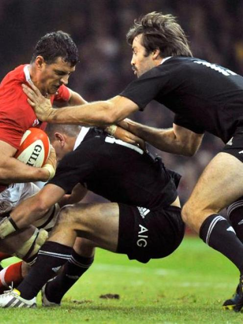 Aaron Shingler of Wales is tackled by All Blacks Aaron Cruden and Conrad Smith. REUTERS/Toby...