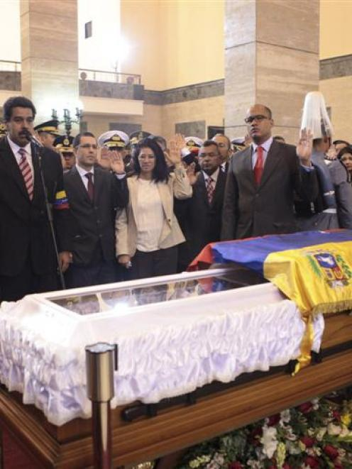 Acting Venezuelan President Nicolas Maduro swears an oath before the coffin of late Venezuelan...