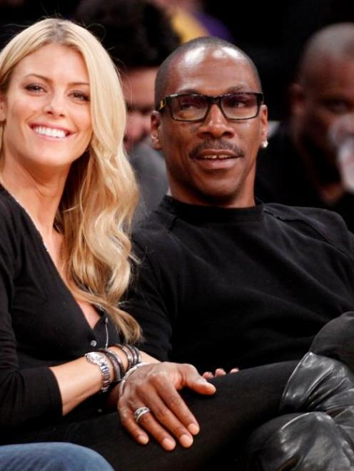 Actor Eddie Murphy with his girlfriend Australian model Paige Butcher courtside at the Staples...