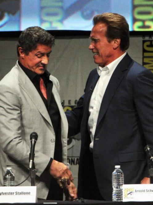 Actors Sylvester Stallone (L) and Arnold Schwarzenegger speak at 'The Expendables 2 Real American...