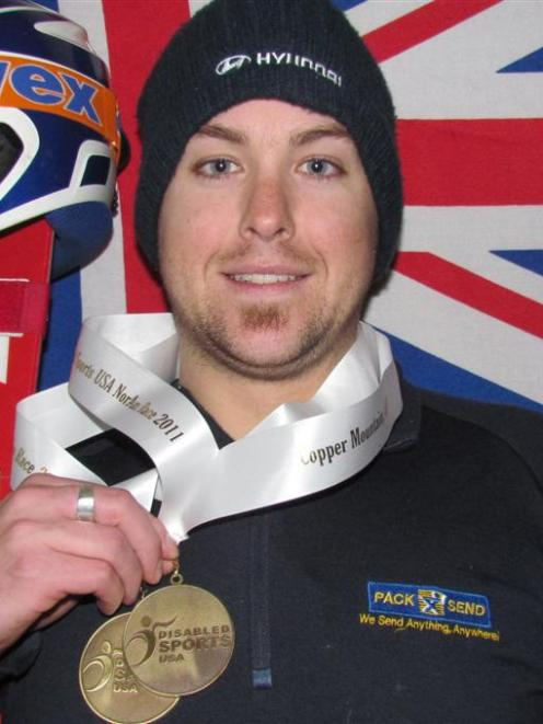 Adam Hall displays the medals he won in the standing slalom competition at the International...
