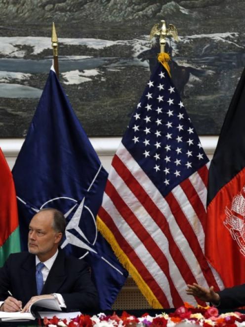 Afghan national security adviser Hanif Atmar (R) and U.S. Ambassador James Cunningham sign the...