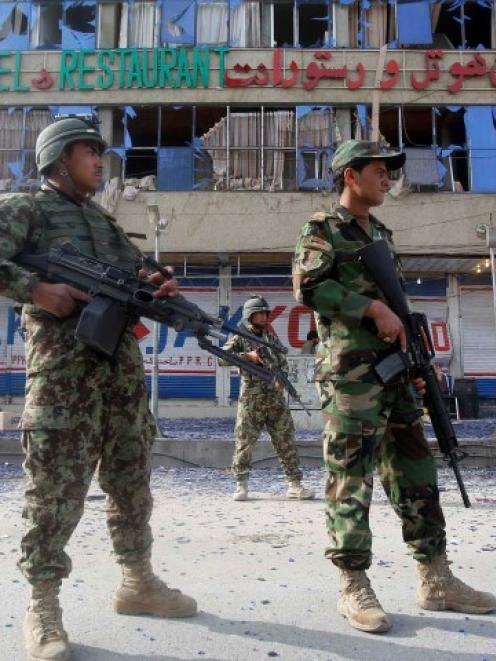 Afghan soldiers stand at the site of a suicide car bomb attack which killed at least 11 people,...