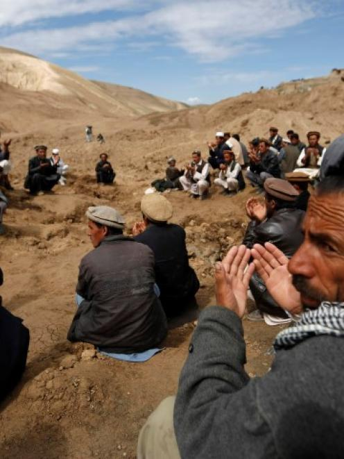 Afghan villagers pray at the site of the landslide at the Argo district in Badakhshan province....
