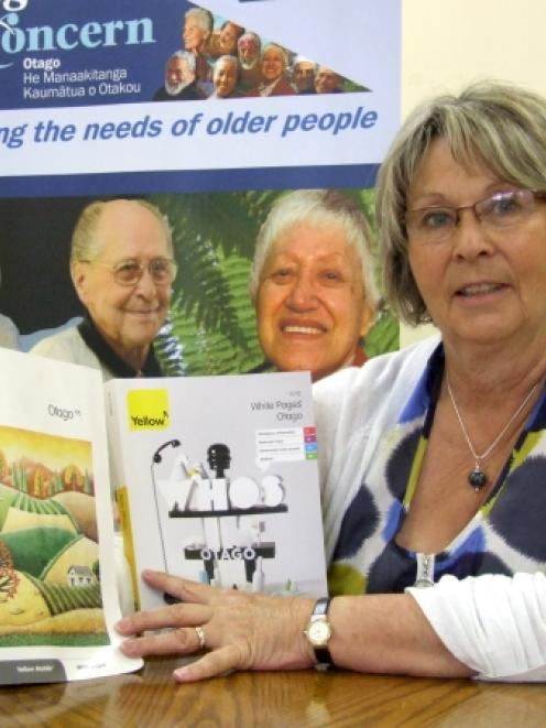 Age Concern Otago chief executive Susan Davidson compares the size of the old and new phone books...