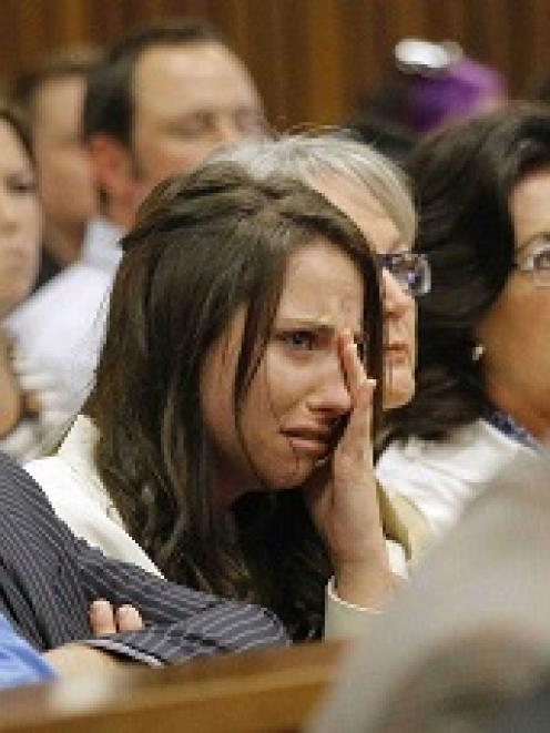 Aimee Pistorius, sister of South African Olympic and Paralympic sprinter Oscar Pistorius, cries...