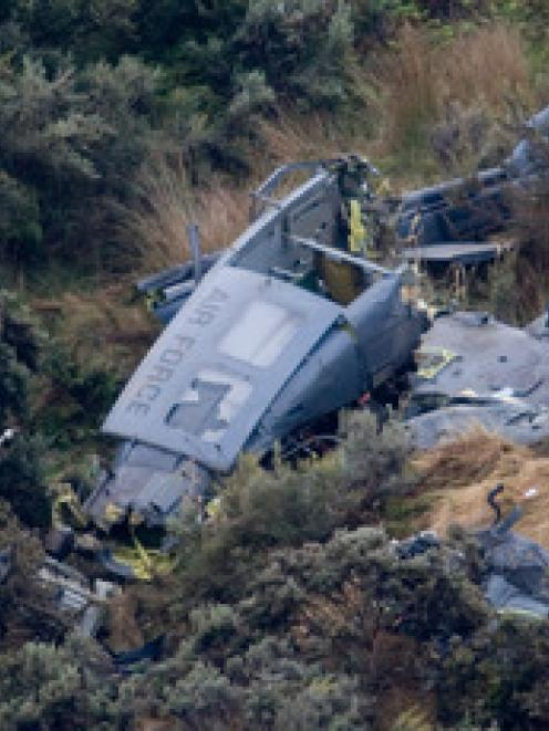 Air force investigators at work around the wreckage of the 3 Squadron Iroquois helicopter which...
