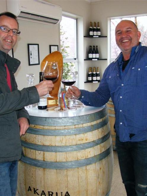 Akarua winemaker Matt Connell (left) and vineyard manager Mark Naismith raise a toast to the...