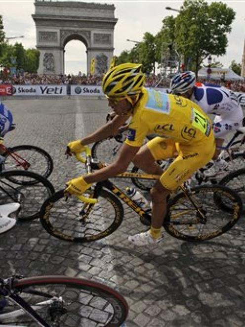 Alberto Contador of Spain, wearing the overall leader's yellow jersey, rides past the Arc de...