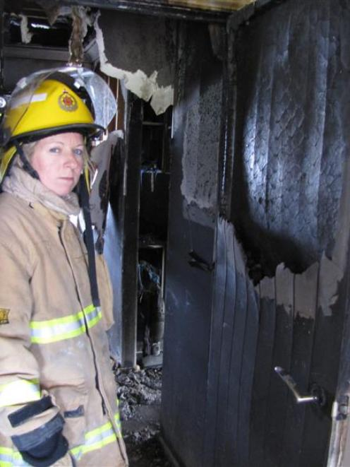 Alexandra firefighter Stacey Waldron shows how closing a door can  trap  a house fire. Photo by...