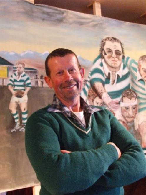 Ali Kingan with the mural he created for the Enfield Rugby Club's reunion. Mr Kingan is wearing...