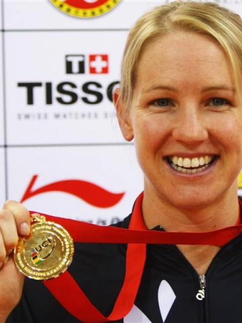 Alison Shanks, of New Zealand, shows off her medal after winning the women's individual pursuit...