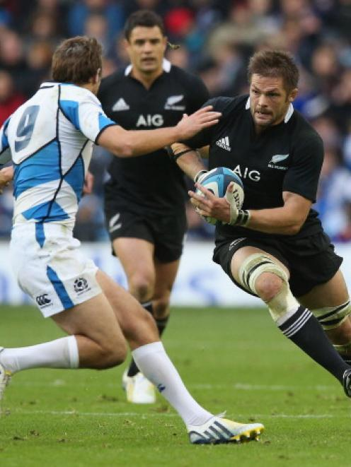 All Black captain Richie McCaw takes on Scotland's Mike Blair during the teams' test at...