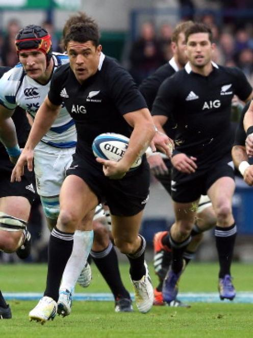 All Black first five Dan Carter charges upfield with teammates in support during the test against...