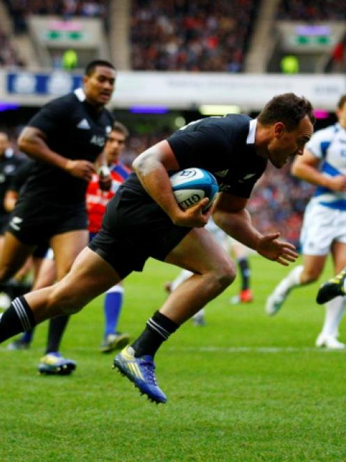All Black fullback Israel Dagg runs in to score a try against Scotland at Murrayfield Stadium in...