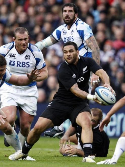 All Black halfback Piri Weepu looks to pass as Scotland players challenge during their test at...
