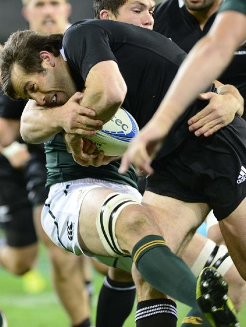 All Black midfielder Conrad Smith is caught by a Springboks tackler during their test match at...