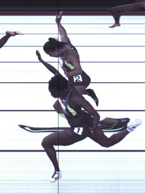 Allyson Felix and Jeneba Tarmoh (front) hit the finish line at the same time during the women's...