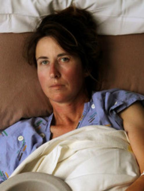 Amanda Austrin, pictured in Tauranga Hospital, still vomits every day - 18 months after her...
