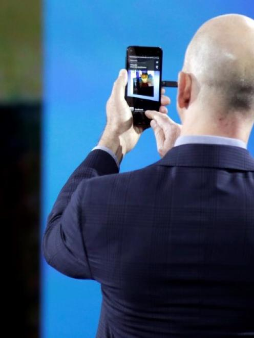 Amazon CEO Jeff Bezos demonstrates features of his company's new Fire smartphone at a news...
