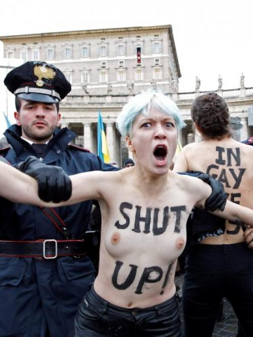 An activist from women's rights protest group Femen is restrained as Pope Benedict XVI leads his...