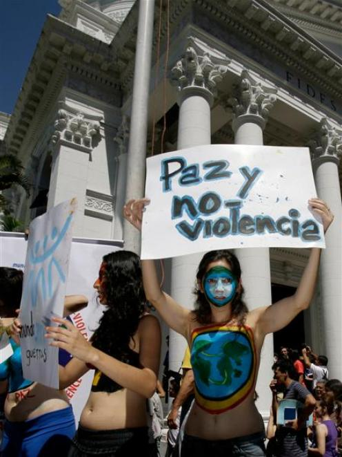 """An activist of the Humanist party holds up a sign reading in Spanish: """"Peace and No Violence"""",..."""