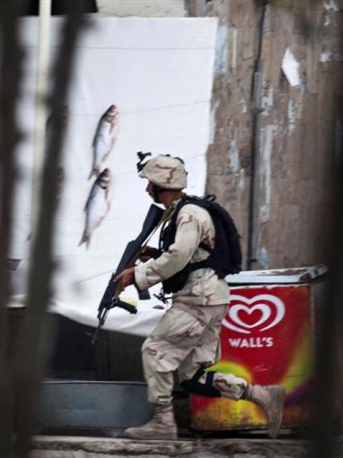 An Afghan counter terrorism personnel runs towards the building which the Taliban insurgents took...