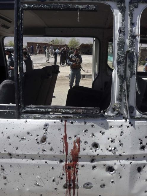 An Afghan policeman is seen through the broken windows of a vehicle after was hit by a remote...