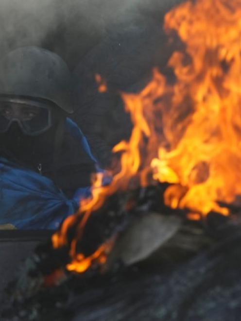 An anti-government protester rests at an open fire as temperatures reach -20degC at a barricade...
