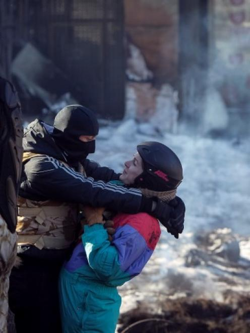 An anti-government protester stands guard as a fellow protester hugs his girlfriend on a...