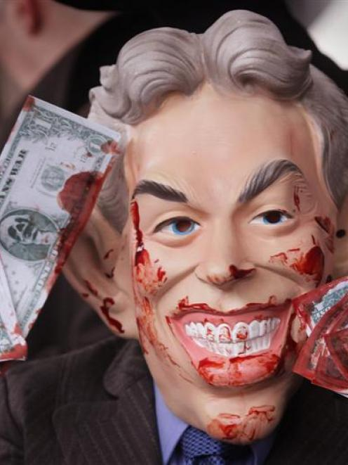 An anti-war demonstrator, dressed as bloodied former British prime minister Tony Blair, stands...