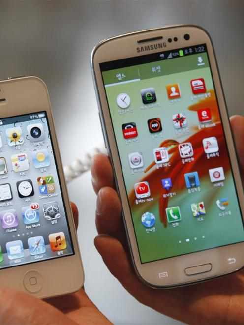An Apple iPhone 4S (left) and a Samsung Galaxy S III. REUTERS/Lee Jae-Won