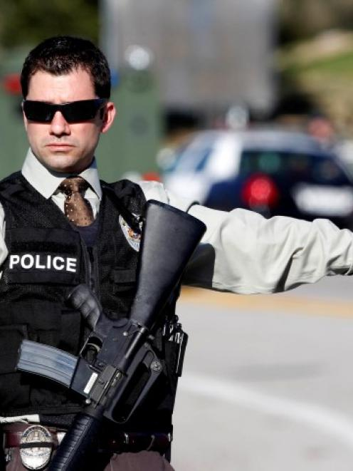 An armed police officer directs traffic in Yucaipa, California, during the manhunt for fugitive...
